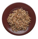 Buckwheat in a plate isolated on white background. buckwheat top view. Healthy food. Buckwheat in a brown  plate isolated on white background. buckwheat top view stock image