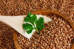 Buckwheat is on the plate with  wooden spoon Stock Photos