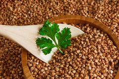 Buckwheat is on the plate with  wooden spoon Stock Photography