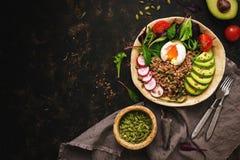 Buckwheat porridge with boiled egg, avocado, radish, chard leaves, arugula, tomato, seeds pumpkins and flax. Buddha bowl with. Healthy food. Top view royalty free stock photos