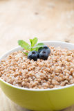 Buckwheat porridge in a bowl with mint leaves and blueberries. Stock Images