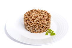 Buckwheat porridge in the form of a circle on a white plate on a white background. Stock Images