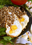 Buckwheat porridge with fried eggs. Royalty Free Stock Images