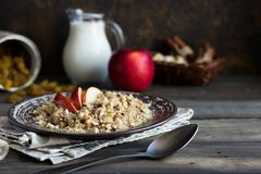 Buckwheat porridge with milk, apple, raisins and cashew nuts. Buckwheat porridge with apples, raisins and cashew nuts for breakfast stock image