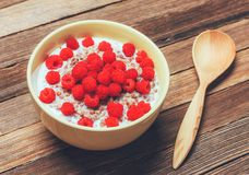 Buckwheat porridge with milk and raspberry berries in a bowl and a wooden spoon on a wooden table, top view. Close-up Royalty Free Stock Image