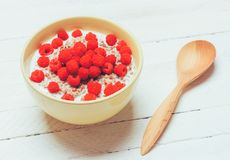 Buckwheat porridge with milk and raspberry berries in a bowl and a wooden spoon on a white wooden table, top view. Close-up Stock Photos