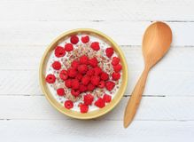 Buckwheat porridge with milk and raspberry berries in a bowl and a wooden spoon on a white wooden table, top view. Close-up Royalty Free Stock Photos