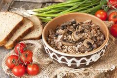 Buckwheat porridge with mushrooms in ceramic pot on table Stock Photography
