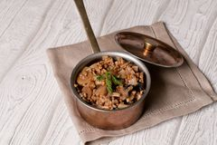 Buckwheat porridge with mushrooms in the copper pan Royalty Free Stock Images