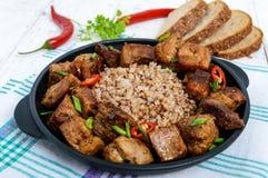 Buckwheat porridge with pieces of fried pork Stock Image