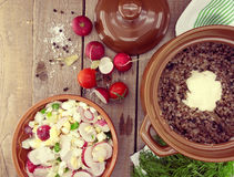 Buckwheat porridge with salad from radish and egg in a ceramic p Royalty Free Stock Image