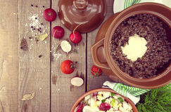 Buckwheat porridge with salad from radish and egg in a ceramic p Stock Photos
