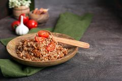Buckwheat porridge with tomato on a wooden plate stock photography