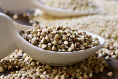 Buckwheat and quinoa seeds. Closeup of some ceramic spoons with different edible seeds such as buckwheat or quinoa, on a rustic wooden surface Stock Photos