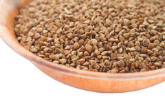 Buckwheat in round wooden plate. Isolated. Stock Photos