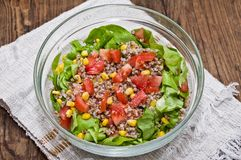 Buckwheat salad for fitness. A glass bowl with buckwheat salad for fitness (buckwheat, lettuce, tomatoes, sweet corn, olive oil, salt royalty free stock photography