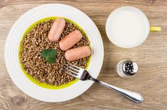 Buckwheat with sausages in plate, milk, salt and fork Royalty Free Stock Images