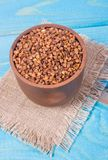 Buckwheat seeds in a ceramic bowl on blue wooden table. royalty free stock photo