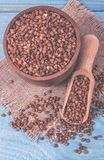 Buckwheat seeds in a ceramic bowl on blue wooden table. stock photo