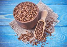 Buckwheat seeds in a ceramic bowl on blue wooden table. stock image