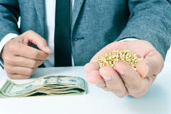 Buckwheat seeds and dollar banknotes, depicting the agribusiness. Closeup of a young caucasian businessman with a pile of buckwheat seeds in his hand and a pile stock photos