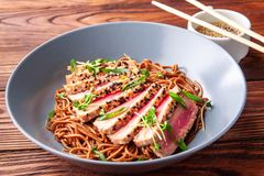 Buckwheat soba noodles with tuna. Japanese buckwheat soba noodles with sliced tuna with sesame on dark wooden table stock photo