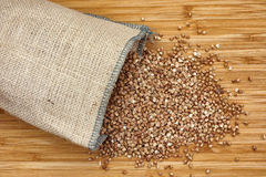 Buckwheat spilling out of burlap bag stock image
