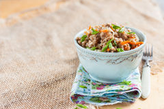 Buckwheat, stewed with meat, carrots and onions on a light background Stock Photography
