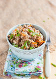 Buckwheat, stewed with meat, carrots and onions on a light background Stock Photo