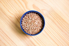 Buckwheat on the table. Bowl full of buckwheat close-up Royalty Free Stock Image