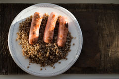 Buckwheat with three grilled Sausage on white plate. Royalty Free Stock Images