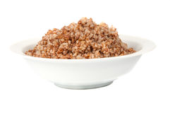 Buckwheat in a white bowl. On white background Stock Photos