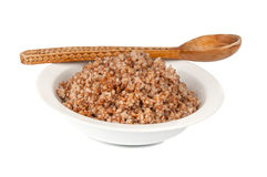 Buckwheat in a white bowl. And wooden spoon Stock Images