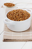 Buckwheat in a white ceramic bowl. On a wooden surface (selective focus Royalty Free Stock Photos