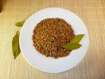 Buckwheat in a white plate on a light background Stock Images