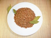 Buckwheat in a white plate on a light background Stock Image