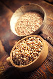 Buckwheat in wooden bowl Stock Photos