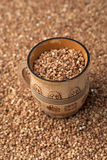 Buckwheat in wooden cup Stock Photo
