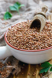 Buckwheat and wooden scoop in a ceramic bowl. Buckwheat and scoop in a ceramic bowl on the old kitchen table, selective focus stock image