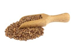 Buckwheat on wooden scoop isolated on white background. Food ingredients: heap of buckwheat in a wooden scoop, on white background stock photo
