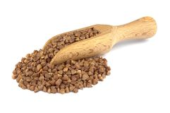 Buckwheat on wooden scoop isolated on white background. Food ingredients: heap of buckwheat in a wooden scoop, on white background stock photography