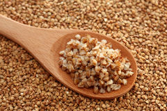 Buckwheat in a wooden spoon. On a buckwheat background. Close-up Stock Photo