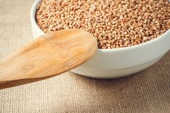 Buckwheat and wooden spoon on burlap background Stock Images