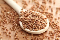 Buckwheat in a wooden spoon royalty free stock photo