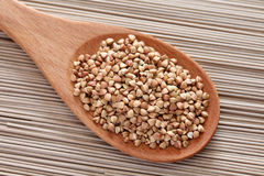 Buckwheat in a wooden spoon on soba noodles background Royalty Free Stock Photography