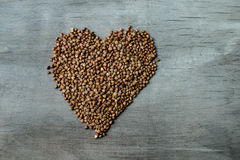 Buckwheats grains formed in heart shape on wooden background. Close up Royalty Free Stock Photography