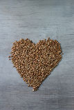 Buckwheats grains formed in heart shape on wooden background. Love Royalty Free Stock Photos