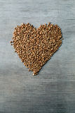 Buckwheats grains formed in heart shape on wooden background Royalty Free Stock Photo