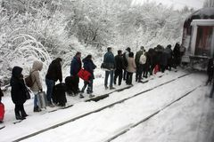 BUCURESTI, ROMANIA-cca 2016 People in a row cross the train rails in heavy snow with luggage in hands t royalty free stock images