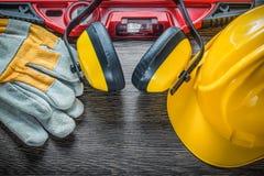 Budów ochronnych rękawiczek ciężkiego kapeluszu równi earmuffs na drewnianym Obrazy Stock